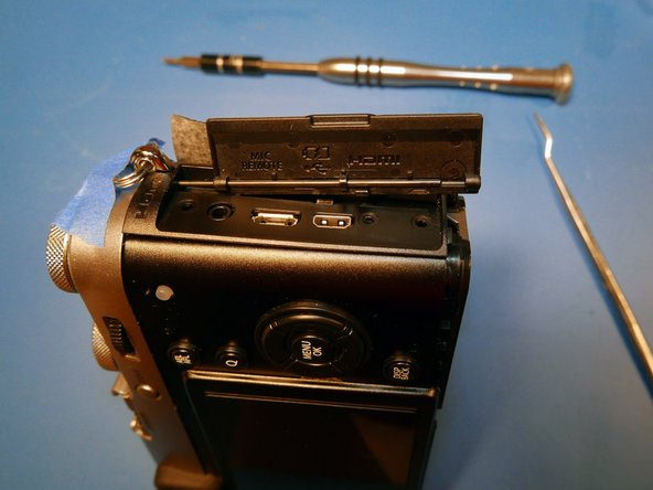 The devil's in the details with this camera. Slide the port cover off the hinge rod.
