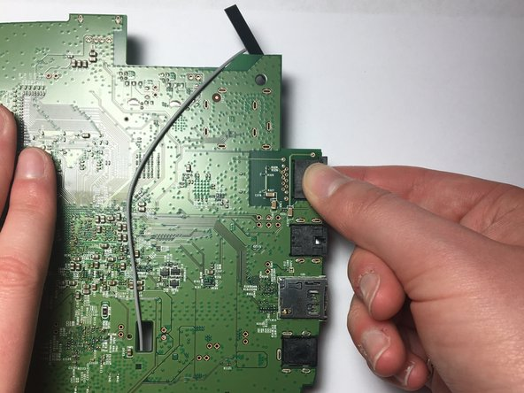 Using your thumb and pointer finger, carefully pinch the Ethernet port and pull it to the right, away from the motherboard, to remove it.