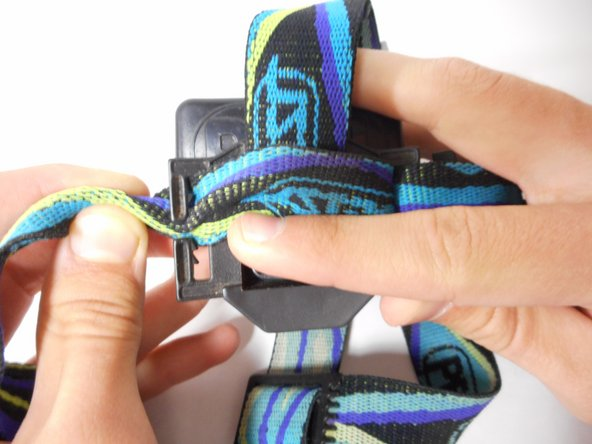 Pull the lefthand portion of the elastic strap through the middle opening.