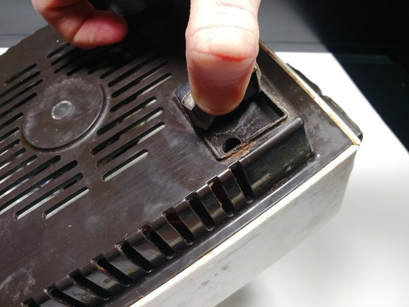 Remove the  four 18 mm Phillips #2 screws from the bottom by prying up the rubber feet to access the screw hole.