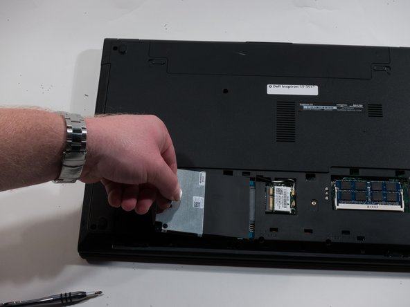 Pull the black tab up and to the left to completely remove the hard drive.