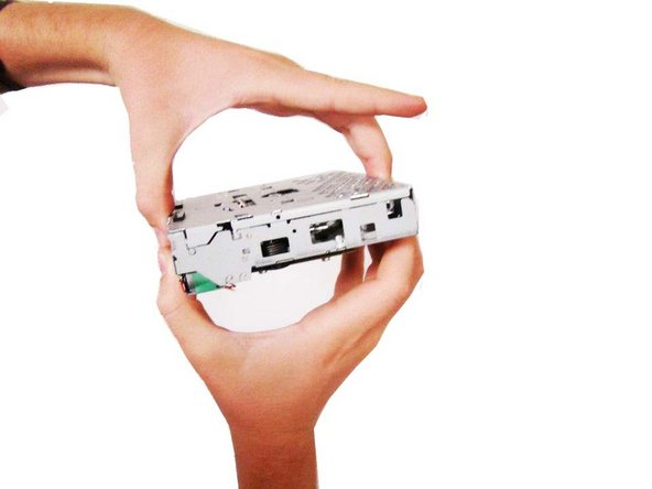 Image 1/3: Grip the top of the CD-Drive and pull it up and over, as shown in the pictures.