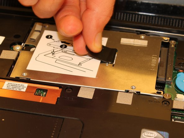 As shown on the top face of the hard drive itself, pull hard drive left using the black tab until the hard drive is unplugged and entirely released from its receptacle.