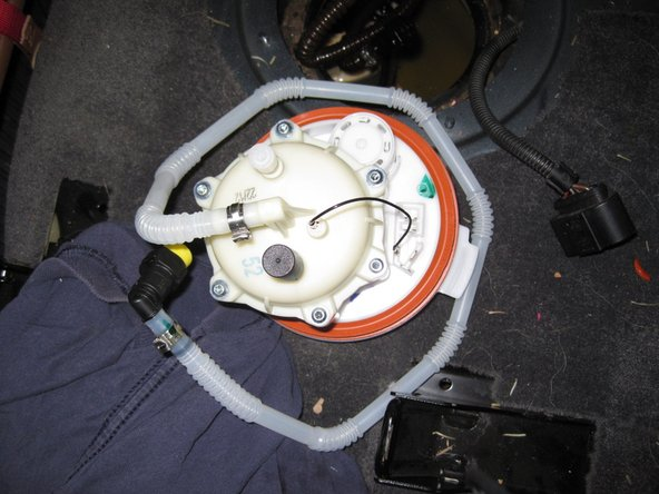 Image 1/2: Temporarily place a new fuel tank gasket on the fuel filter assembly (the gasket is orange)