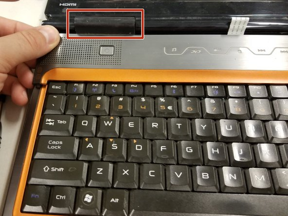 Using a pair of tweezers, your fingers, or a screw driver, carefully dig into the laptop cover and apply force to pop it out.
