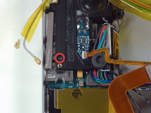 Remove the single black T6 Torx screw securing the left speaker.