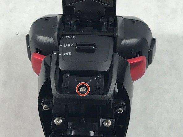 Push the lock switch upward and remove the 6 mm screw hidden beneath.