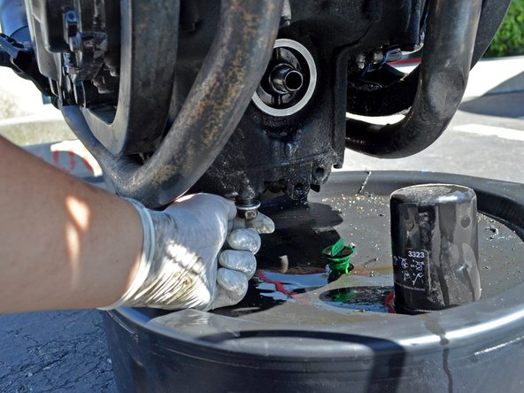 Once the draining oil has slowed to a drip, clean the area around the drain plug hole with a clean towel or rag and replace the oil drain plug.