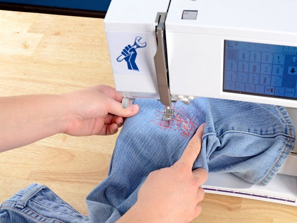 Image 1/2: Slide the pant leg off the arm of the sewing machine.
