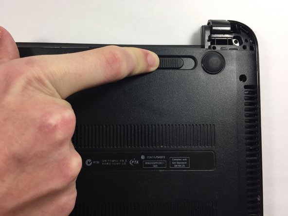 Push the slide on the right toward the center of the laptop, releasing the battery latch.