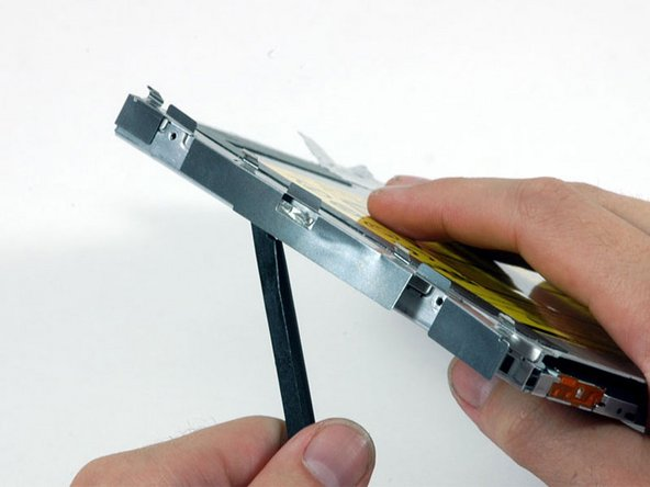 Image 1/1: Use a spudger to carefully pry the silver metal bracket off the left side of the optical drive. Be careful not to bend the bracket, as it is very thin and bends easily. If the bracket doesn't come free easily, heating the adhesive may make prying the bracket off easier.