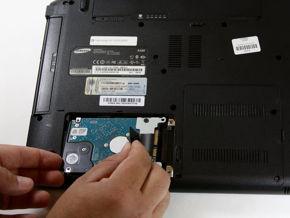 Grasp the tab and pull it to the left until the hard drive releases its connection and is able to be lifted free.