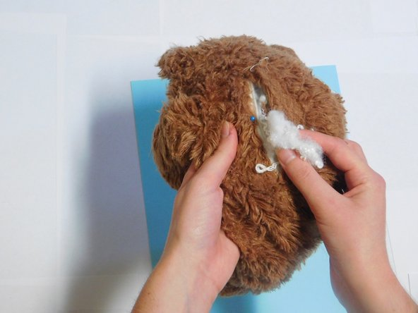 Remove all of the stuffing through the created incision and set it nearby to use later.