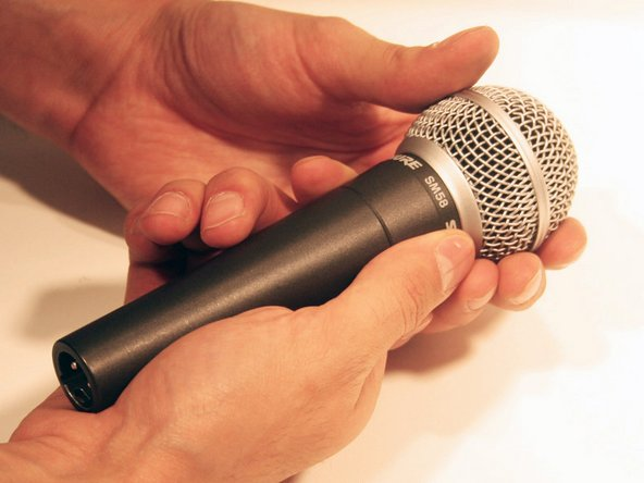 Hold the microphone just below the grille with one hand while using your other hand to rotate the grille clockwise to remove.