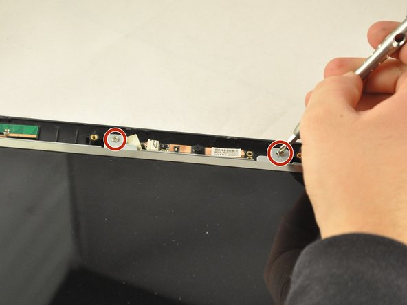 Using the PH1 screwdriver, remove the  two .75 cm screws from the top of the screen frame.