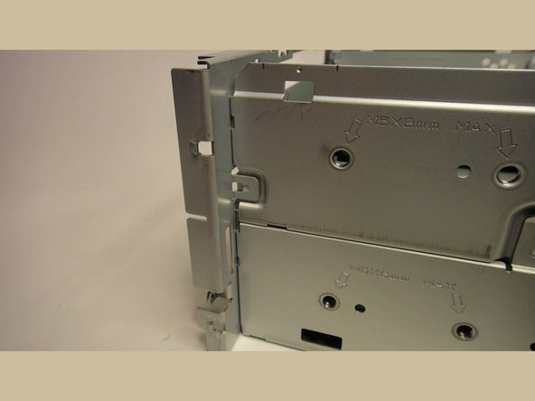 Use a small flat bladed screwdriver to release the metal tabs which hold the front panel onto the upper case.