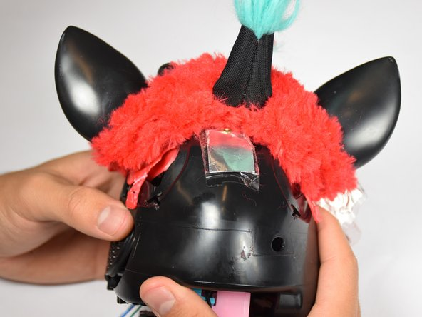 Remove the loose, plastic back panel by pulling the panel away from Furby's body.