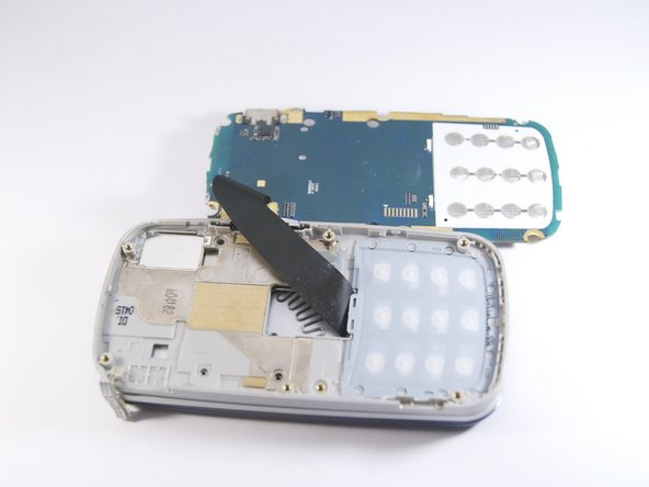 Carefully lift up the motherboard to expose the back of the keypad.