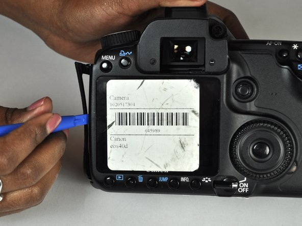 Image 1/2: Use a plastic opening tool to gently start prying the rear case up from the rest of the camera.