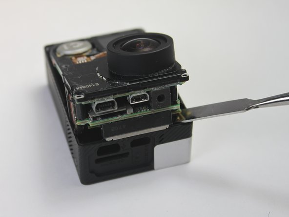 To avoid breaking the plastic on the lens side of the camera (see photo), pry along the edges near the corners.
