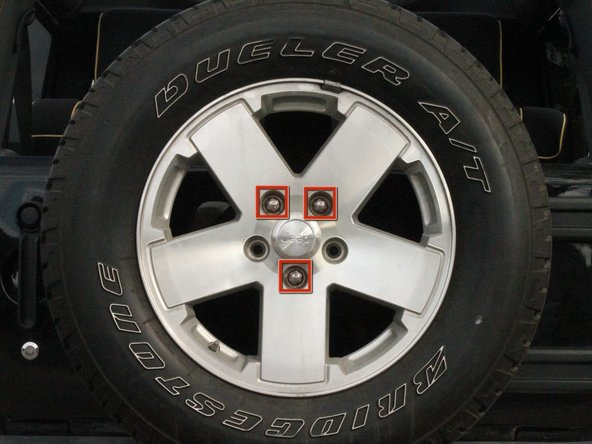 Image 1/2: Push hard in a counter-clockwise motion to remove the three lug nuts using the lug wrench.