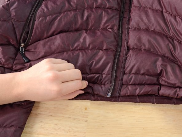 Unzip the jacket and fold back the bottom corner.