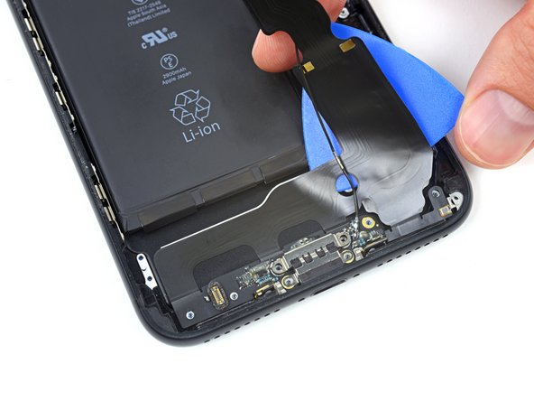 Slide your pick across the width of the iPhone to separate all the remaining strands of the flex cable from the rear case.