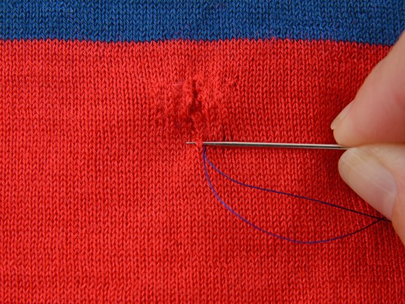 Take another straight stitch towards the hole, going in and out of a single layer of the garment, passing the thread under a single row of the knit.