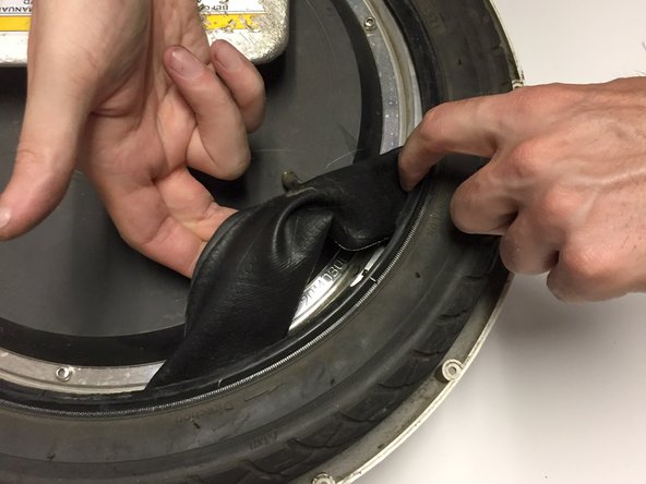 Reach into the rubber tire and remove the old rubber inner tube.