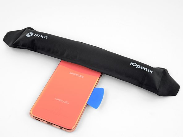 Apply a heated iOpener to the top edge of the phone for two minutes.