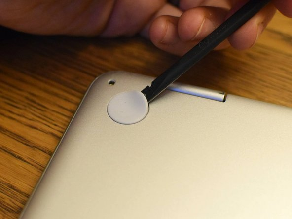 Using a spudger (or prying tool, or fingernail), gently lift the feet at the rear of the laptop (near the hinges). Get underneath the pad, then release the adhesive by sweeping in a circular motion.