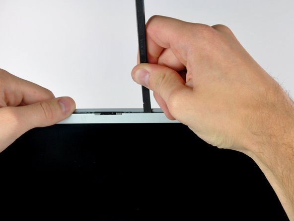 Insert a spudger just to the right of the hinge opening on the top edge of the display between the front display bezel and the plastic strip attached to the rear bezel.