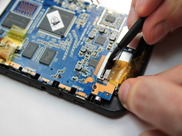Image 2/3: Gently pull the tape attached to the ribbon cable to remove the cable from its socket.