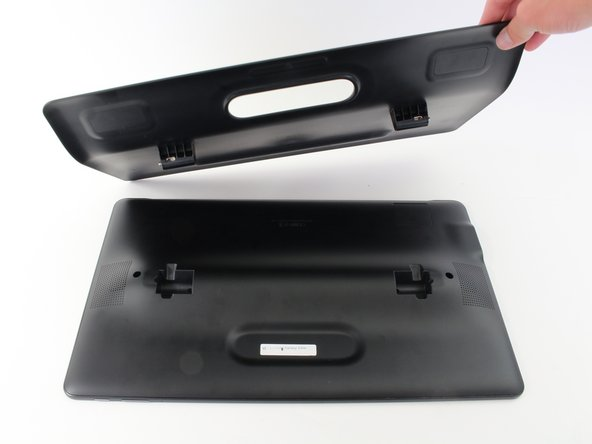 Once the latch is moved to the right pull up on the left side of the kickstand releasing it from the back of the tablet.