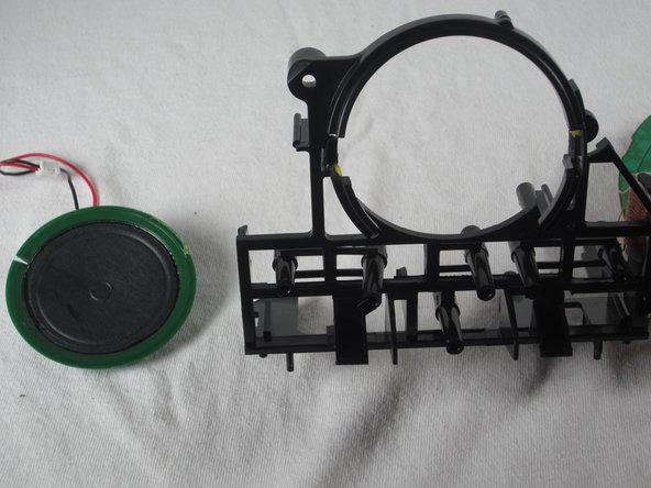 With a small amount of force, push on the plastic clips, away from you, to eject the speaker from its plastic housing.