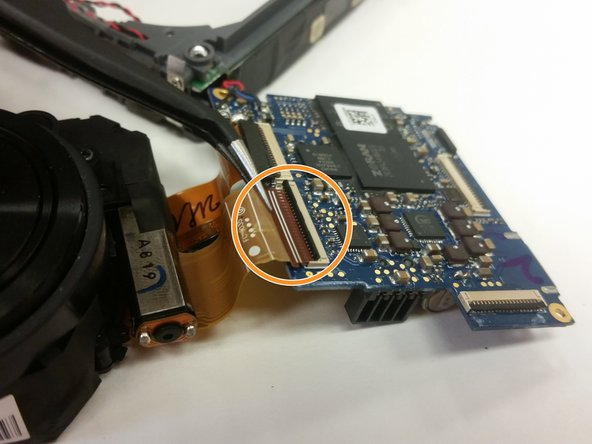 Use the Tweezers to remove the first large lens unit cord from the motherboard.