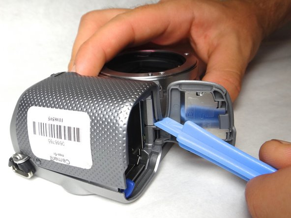 Use the spudger to raise the corner of the case from the camera.