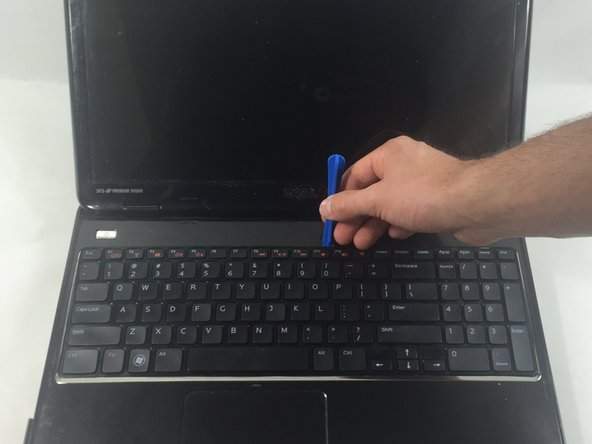 Pry the keyboard away from the device using the plastic opening tool.