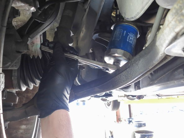 Use the oil filter wrench to loosen the oil filter, then unscrew it the rest of the way by hand.