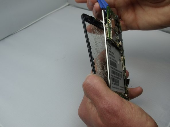 Use your pick to separate screen from the LCD and motherboard.
