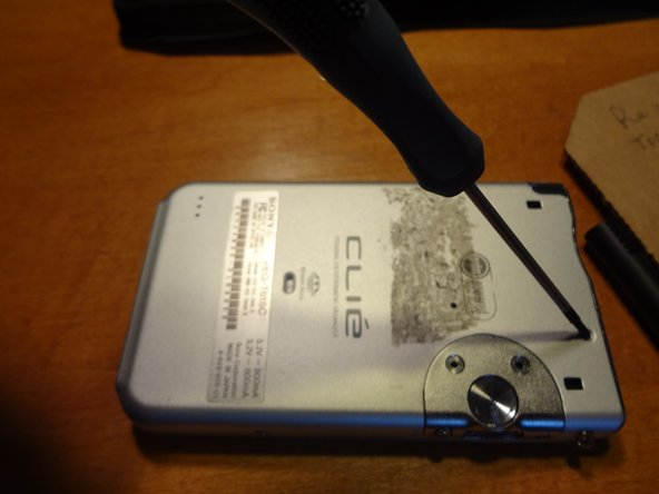 Remove one screw from the upper right corner on the back of the device.