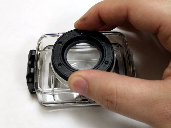 While holding the black lens cover trim tight to the case, flip the case over so that the lens cover is rested on your work surface.