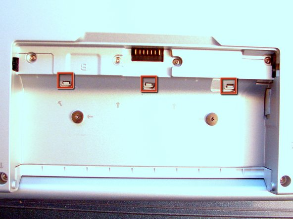 Image 1/2: To do so, we need to lever the 3 pins in the battery bay (marked red). Do it gently not to brake them.
