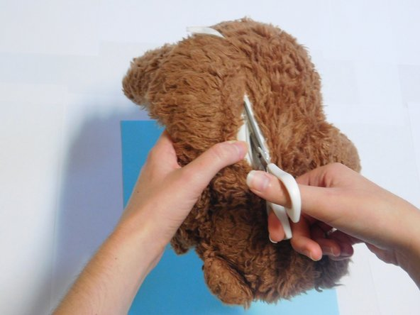 Using a pair of scissors, make an incision approximately 3 inches in length along the middle major seam on the back of the stuffed animal (a seam ripper may also be used to open an existing seam).
