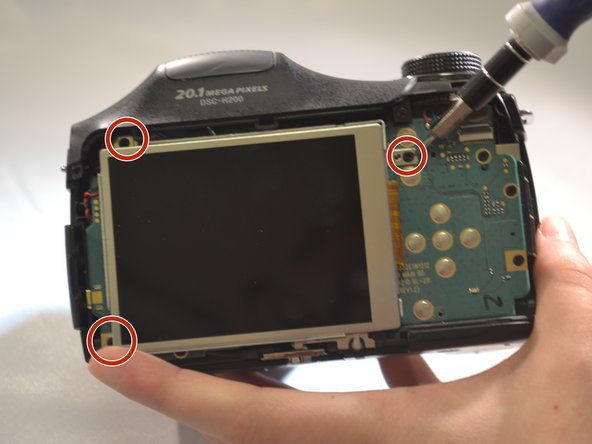 Using a screwdriver, remove the three 4mm screws that attach the LCD to the camera motherboard (The LCD is contained in a holding plate, attached to the motherboard with a ribbon cable).