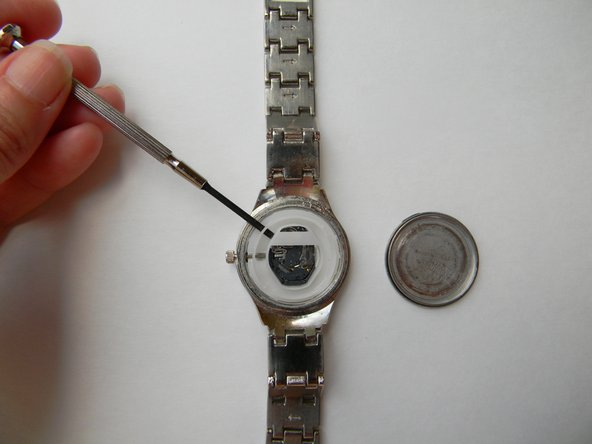 Take the white plastic ring out of the watch. You can use the mini flat head screwdriver or your finger to pull it out.