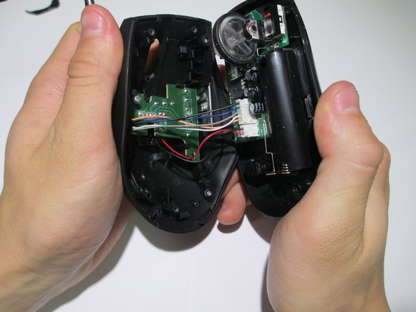 Pry the center of the mouse apart to separate the upper and lower housing of the boards.