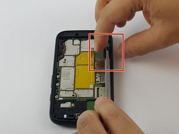 Image 1/3: Using the metal spudger tool, gently pull up the right corner as indicated and work your way around until it's off the motherboard.