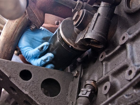 Image 2/3: If your oil filter is stuck, you may need an oil filter strap wrench to remove it. They can be found at most auto parts stores. In a bind, you can also hammer a flathead screwdriver through the body of the filter to gain leverage (this process is messy).