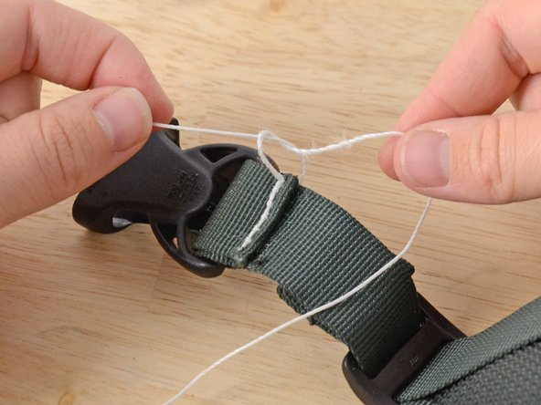 Tie an overhand knot with the two ends of the thread.